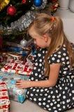 Mädchenöffnung Weihnachtsgeschenk unter Weihnachtsbaum Stockfotos