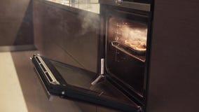 Mädchen öffnet Ofen und nimmt gebrannte Plätzchen, Rauch von übergekochtem Lebensmittel kommt stock video footage