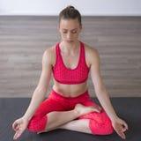 Mädchen in übendem Yoga des Lotussitzes stockbild