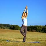 Mädchen-übendes Yoga auf dem Gebiet Stockfotos