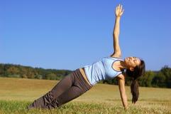 Mädchen-übendes Yoga auf dem Gebiet stockfotografie