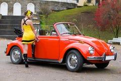 Mädchen über ein Retro- Auto Stockfotografie