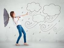 Mädchen über einer weißen Wand, Konzept des falschen Wetters Stockfotos
