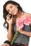Mädchen über Mobiltelefon mit rosafarbenen Gänseblümchenblumen lizenzfreie stockfotos