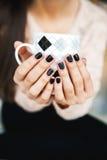 Mädchen übergibt das Halten eines Tasse Kaffees mit schöner schwarzer Maniküre Weihnachten Stockfoto