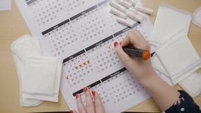 Mädchen übergibt die Berechnung ihrer Ovulation und die Markierung der Daten an einem Kalender mit einer Markierung, beim Fragen, stock video