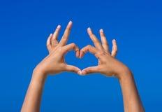 Mädchen übergibt die Formung ist Herz für Liebe mit blauem Himmel Lizenzfreies Stockbild