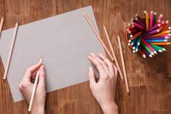 Mädchen übergibt Zeichnung, gelbes Papier des freien Raumes und bunte Bleistifte auf altem Holztisch Stockbild
