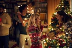 Mädchen überraschend ihr Freundmädchen mit einem Geschenk am Weihnachten lizenzfreie stockfotos