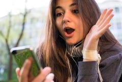 Mädchen überrascht durch Mitteilung auf Mobile Lizenzfreies Stockfoto