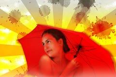 Mädchen abgedeckt mit einem roten Regenschirm Lizenzfreie Stockfotografie