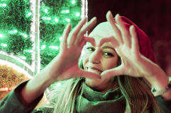 Mädchen als Santa Claus, die Herzform zeigt stockfotos