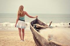 Mädchen am alten Fischerboot, das zum Ozean schaut Stockfotografie