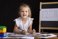 Mädchen-Architekt, der hinter einem Schreibtisch und Blicken in einem Rahmen sitzt Stockfoto
