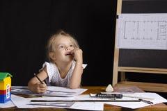 Mädchen-Architekt sitzend hinter einem Schreibtisch und träumerisch gedacht Lizenzfreies Stockbild