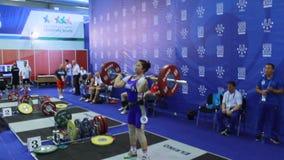Mädchen-Athlet in blauem und weißem Triko hebt Gewicht an stock footage