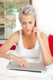 Mädchen auf Bett mit Laptop beim Hören auf Telefon Stockfoto