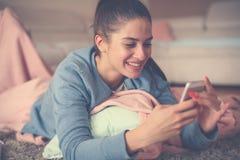 Mädchen auf Boden schreibend am intelligenten Telefon Abschluss oben stockfotos