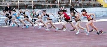 Mädchen auf dem Anfang der 100 Meter laufen Stockbild