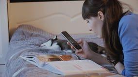 Mädchen auf dem Bett mit dem Telefon, der Welpe des sibirischen Huskys, der neben ihr schläft stock video