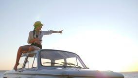 Mädchen auf dem Dach der alten Maschine nahe Fluss mit Gerät in der Hand, weiblich zum Weinleseautomobil auf Hintergrundbeleuchtu stock footage