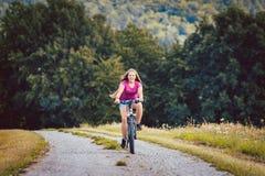 Mädchen auf dem Fahrrad, das einen Erdweg im Sommer ausläuft Lizenzfreies Stockbild