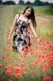 Mädchen auf dem Feld mit Mohnblumeblumen Stockbild