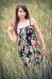 Mädchen auf dem Feld mit Mohnblumeblumen Stockbilder
