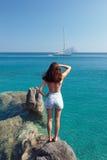 Mädchen auf dem Felsen, der zur Yacht auf Meer schaut Lizenzfreies Stockfoto