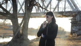 Mädchen auf dem Hintergrund der Brücke raucht eine e-Zigarette, Transportwagen stock video footage