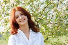 Mädchen auf dem Hintergrund eines blühenden Baums Lizenzfreies Stockbild