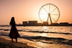 Mädchen auf dem JBR-Strand mit Ain Dubai-Riesenrad Lizenzfreies Stockfoto