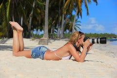 Mädchen auf dem karibischen Strand mit einer Kamera Stockbild