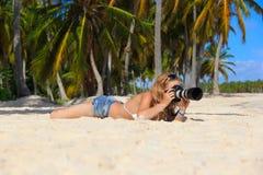 Mädchen auf dem karibischen Strand mit einer Kamera Stockfotografie