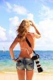 Mädchen auf dem karibischen Strand mit einer Kamera Lizenzfreies Stockbild