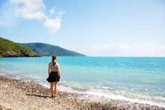 Mädchen auf dem korallenroten Strand, der heraus zum Meer schaut Stockfotografie