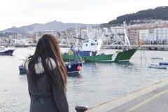Mädchen auf dem Seehafen, die Boote betrachtend Stockbilder