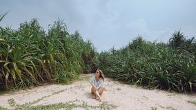 Mädchen auf dem Strand auf dem Hintergrund von tropischen Anlagen Lizenzfreies Stockbild
