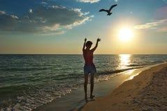 Mädchen auf dem Strand bei Sonnenuntergang Stockbilder