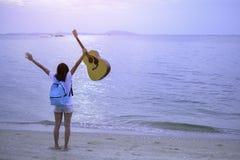 Mädchen auf dem Strand, der Gitarre obenliegend, Feiertags-Mädchen-Konzept hält Lizenzfreie Stockfotografie