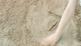 Mädchen auf dem Strand durch das Wasser auf Sand zeichnet stock footage