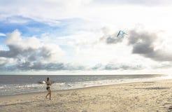 Mädchen auf dem Strand mit Drachen stockfoto