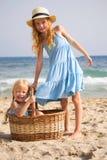Mädchen auf dem Strand mit einem Korb lizenzfreie stockbilder