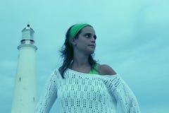 Mädchen auf dem Strand mit einem Leuchtturm Stockbilder