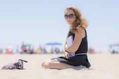 Mädchen auf dem Strand mit einem Notizbuch lizenzfreies stockfoto
