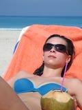 Mädchen auf dem Strand mit Kokosnussgetränk Lizenzfreie Stockfotos