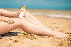 Mädchen auf dem Strand mit Sonnenschutzmittel Lizenzfreie Stockfotos