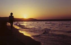 Mädchen auf dem Strand am Sonnenuntergang Stockfotografie