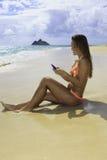 Mädchen auf dem texting Strand Lizenzfreies Stockfoto