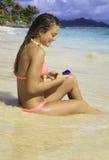 Mädchen auf dem texting Strand Stockfoto